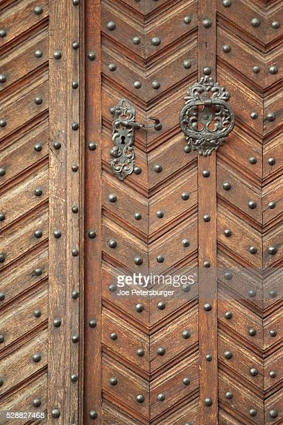 Wooden door with rivets and ornate knocker of a historical building