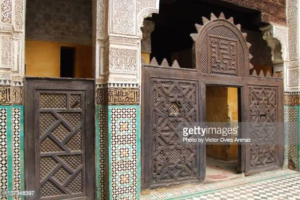wooden doors and tiles of the the madrasa bou inania in meknes, morocco - victor ovies fotografías e imágenes de stock
