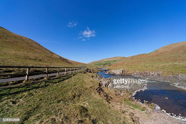 A wooden fence along a road with a stream running through the hills; cheviots northumberland england