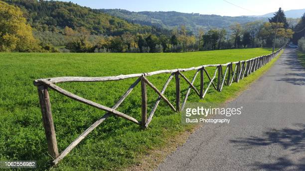 Wooden fence along rural road in rural Tuscany, Italy