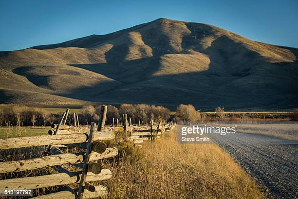 wooden fence and rural field near mountain - sun valley idaho stock photos and pictures