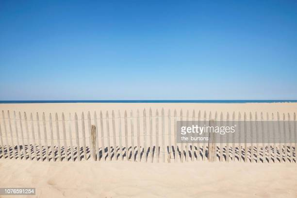 wooden fence at the beach against sea and blue sky - biarritz stock pictures, royalty-free photos & images