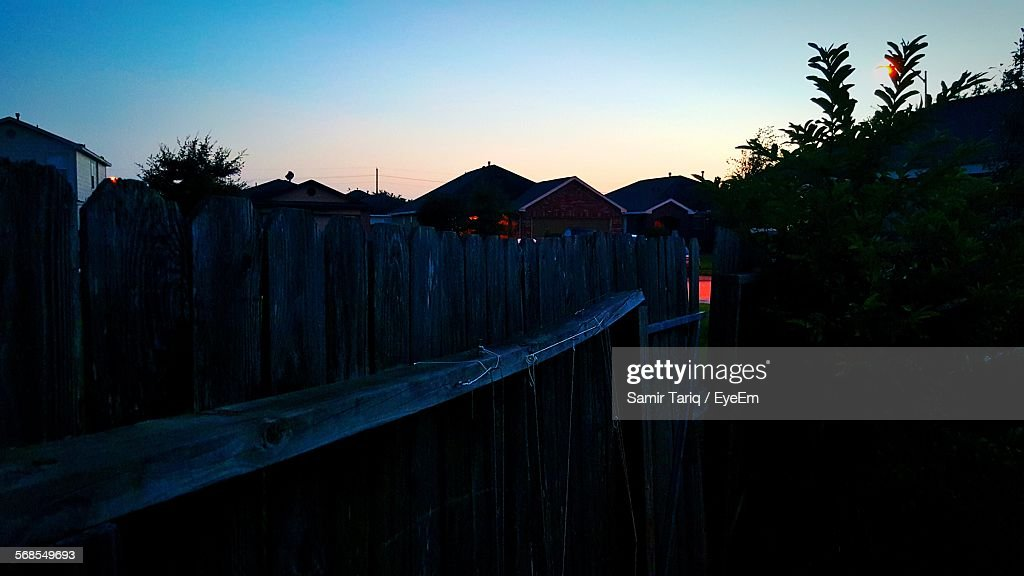 Wooden Fence By Houses Against Clear Sky At Dusk : Stock Photo