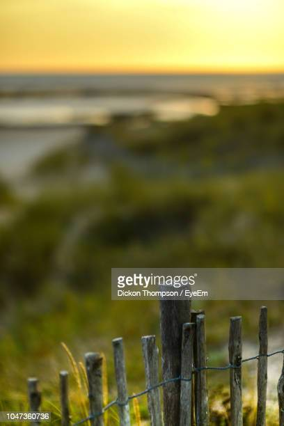 Wooden Fence On Field Against Sky During Sunset