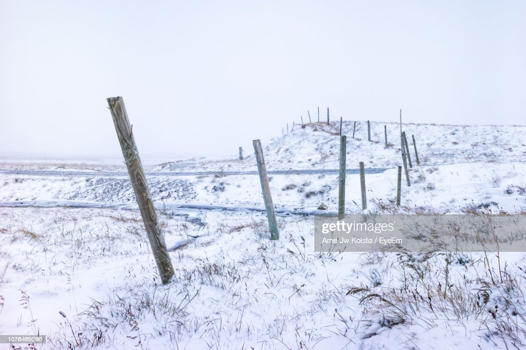 Wooden Fence On Snow Covered Field Against Sky : Stock Photo