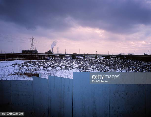 Wooden fence with bare terrain, expressway and power plant