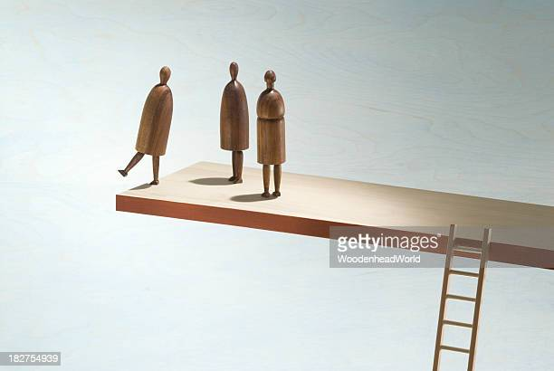 Wooden figures on the edge of a wooden shelf with ladder