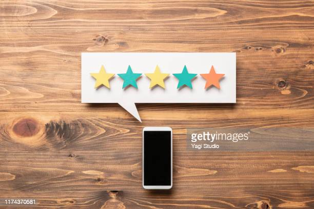 wooden five star shape with chat bubble and smart phone. - marquer photos et images de collection