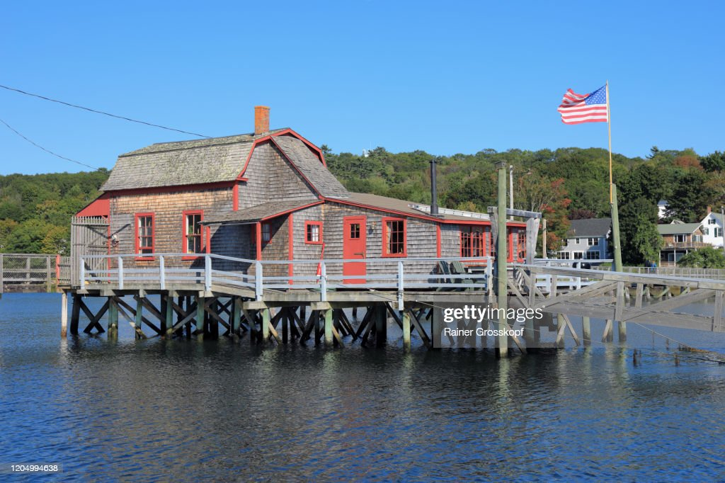 A wooden footbridge across a bay in a small town with a wooden buidling on the middle of the bridge : Stock-Foto