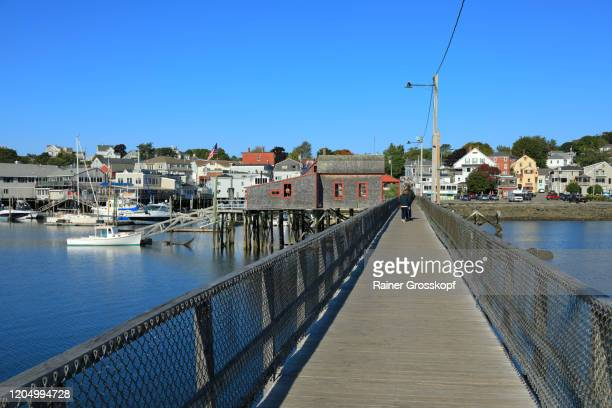 a wooden footbridge across a bay in a small town with a wooden buidling on the middle of the bridge - rainer grosskopf stock pictures, royalty-free photos & images