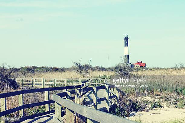 Wooden Footbridge On Grassy Field By Lighthouse Against Sky