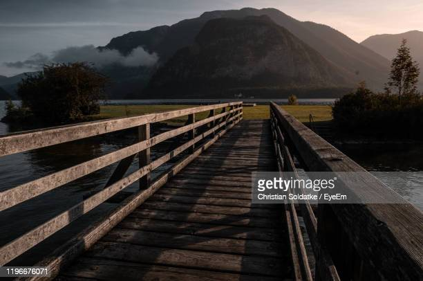 wooden footbridge over river leading towards mountains against sky - christian soldatke stock pictures, royalty-free photos & images