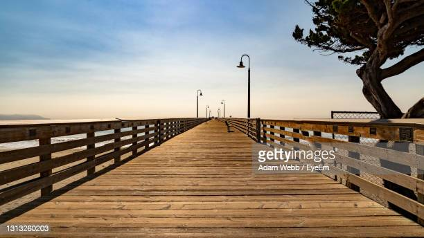 wooden footbridge over sea against sky during sunset - cayucos stock pictures, royalty-free photos & images