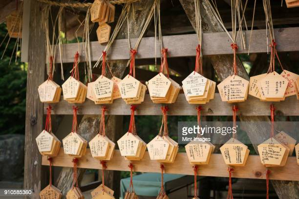 wooden fortune telling plaques at shinto sakurai shrine, fukuoka, japan. - shrine stock pictures, royalty-free photos & images