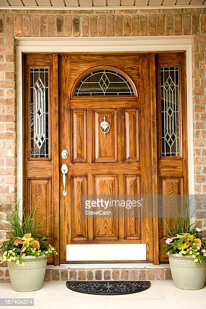 wooden front door of a brick house with two flower pots - brass stock pictures, royalty-free photos & images