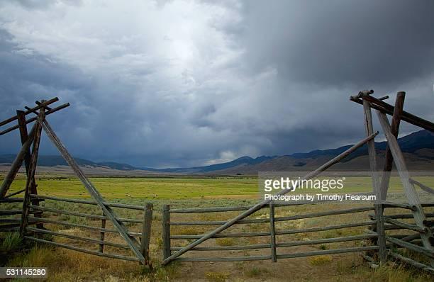 wooden gates with round bales of hay, mountains and storm clouds beyond - timothy hearsum stock-fotos und bilder