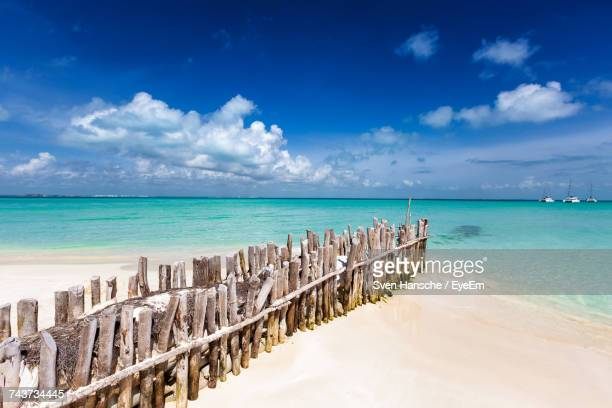 wooden groyne on shore at beach against sky - isla mujeres ストックフォトと画像