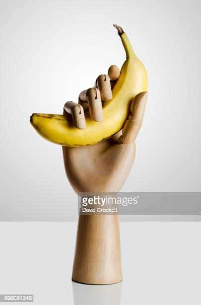Wooden hand holding a banana