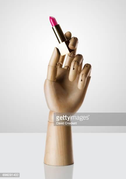 Wooden hand holding lipstick