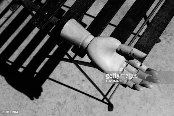 Wooden hand on chair in sunlit scene.