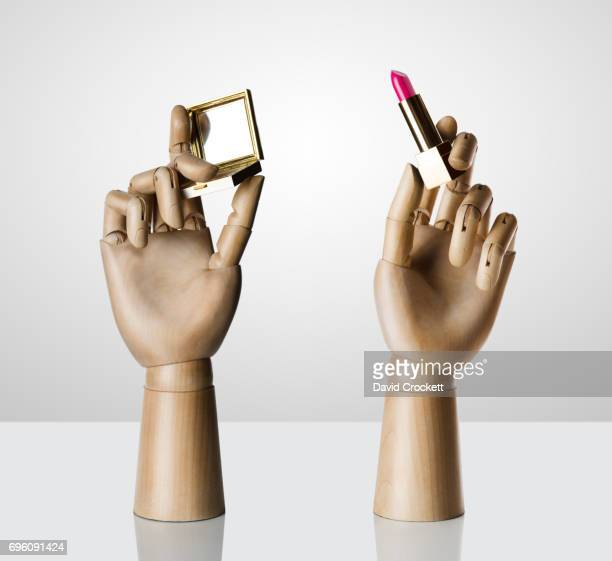 Wooden hands holding lipstick and powder compact.
