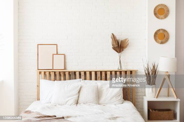 wooden headboard with dry gold palm leaves in a glass vase and two photo frames on it. stylish trendy decoration with copy space. - beige stock pictures, royalty-free photos & images