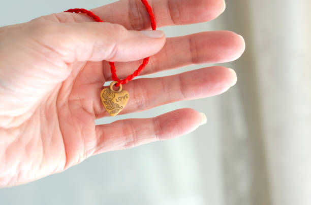 Wooden heart bracelet with word 'love' engraved hanging on a woman's hand