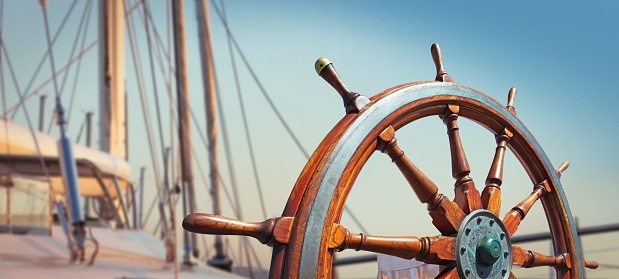 Wooden helm on the yacht 1022935712