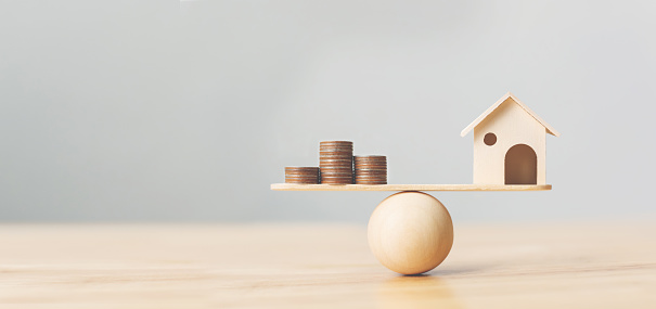 Wooden home and money coins stack on wood scale. Property investment and house mortgage financial real estate concept 1136482657