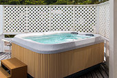 Wooden hot tub with swirling water at outdoor.