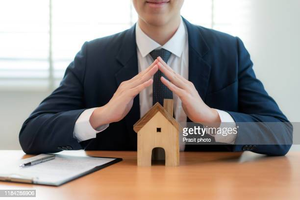 wooden house covered by real estate insurance broker agent man hands protecting gesture of man and symbol of house. property insurance and security concept. - security_(finance) stock pictures, royalty-free photos & images