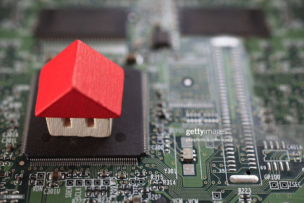 Wooden house on top of circuit board : Stock Photo