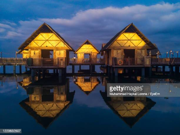 wooden houses with reflection by laguna lake against sky - lorena day stock pictures, royalty-free photos & images