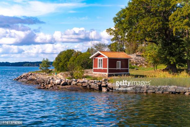 wooden hut in traditional red at the archipelago near stockholm, sweden - shack stock pictures, royalty-free photos & images