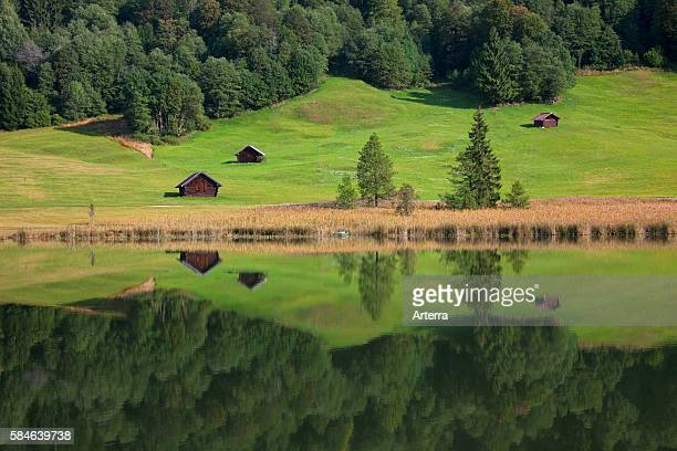 Wooden huts and reflection of pine forest in water along lake Gerold / Geroldsee near Mittenwald, Upper Bavaria, Germany.
