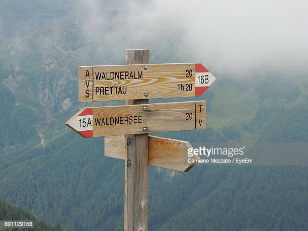 wooden information signs against mountain - directional sign stock pictures, royalty-free photos & images