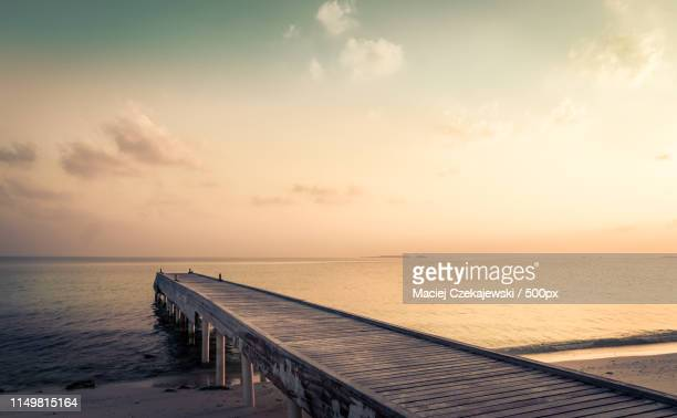 wooden jetty and amazing sunrise in maldives - jetty stock pictures, royalty-free photos & images