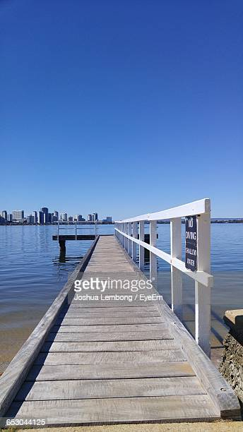 Wooden Jetty Leading To Calm Blue Sea