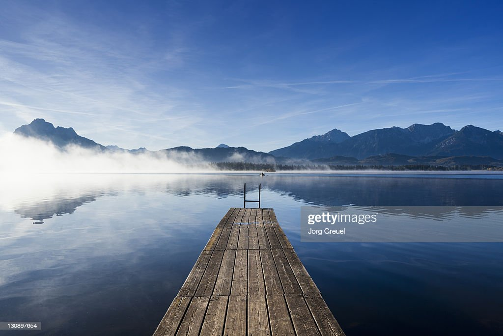 A wooden jetty on Lake Hopfensee at sunrise : Stock Photo
