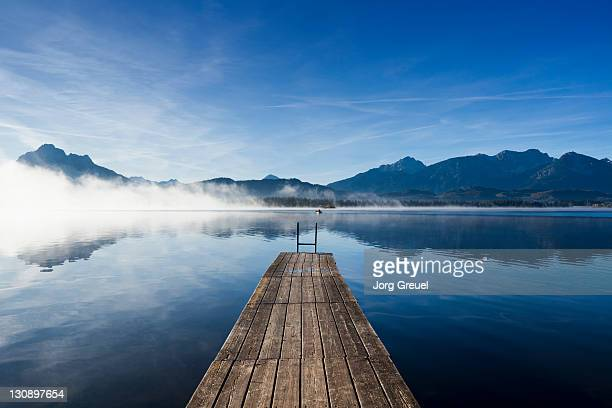 a wooden jetty on lake hopfensee at sunrise - lago imagens e fotografias de stock