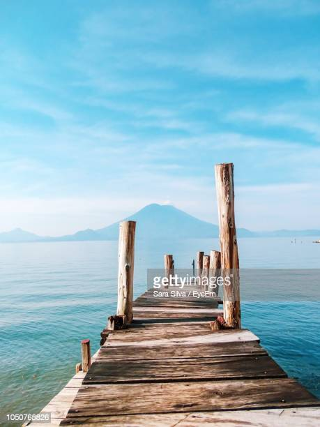 wooden jetty on pier over sea against sky - jetty stock pictures, royalty-free photos & images