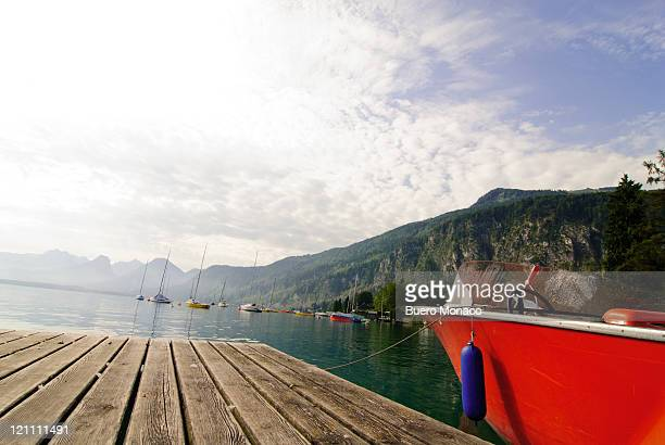 wooden jetty with motor boat, mountains
