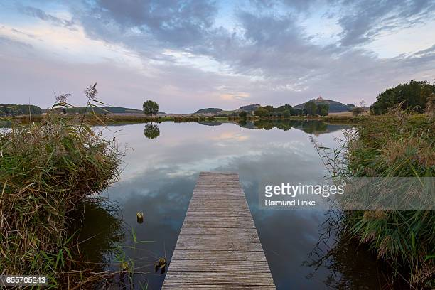 wooden jetty with reflective sky in lake - テューリンゲン州 ストックフォトと画像