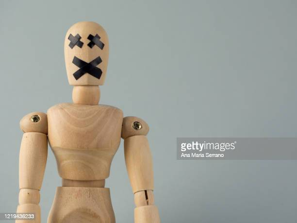 a wooden jointed doll with an x of duct tape covering its mouth and eyes - extremismo imagens e fotografias de stock