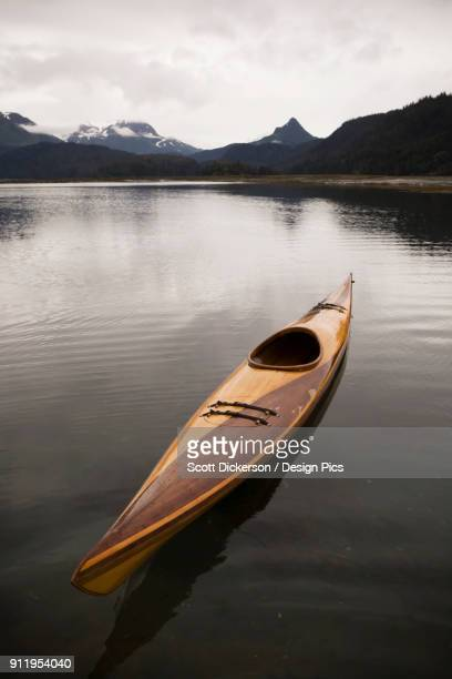a wooden kayak sits on tranquil water with a view of the mountains in the background, kachemak bay state park - kachemak bay stock pictures, royalty-free photos & images