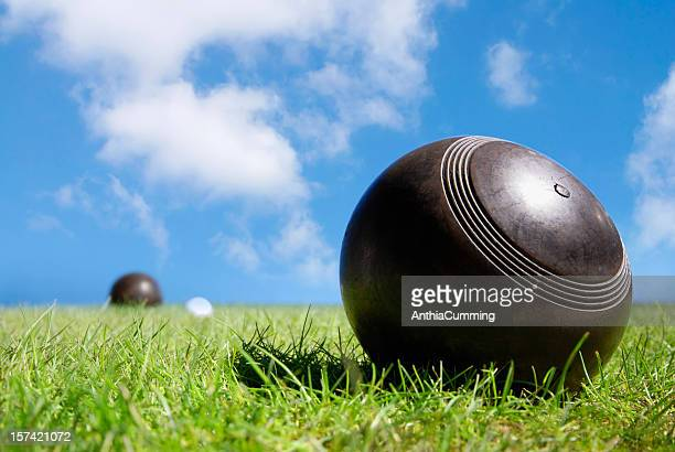 Wooden lawn bowls green grass under blue sky