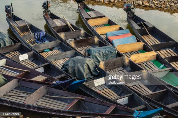 wooden long boats parked at kuala tembeling jetty. - shaifulzamri stock pictures, royalty-free photos & images