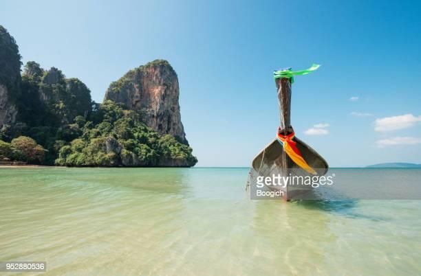 hölzerne longtail-boot in tropical railay beach in krabi thailand - railay strand stock-fotos und bilder