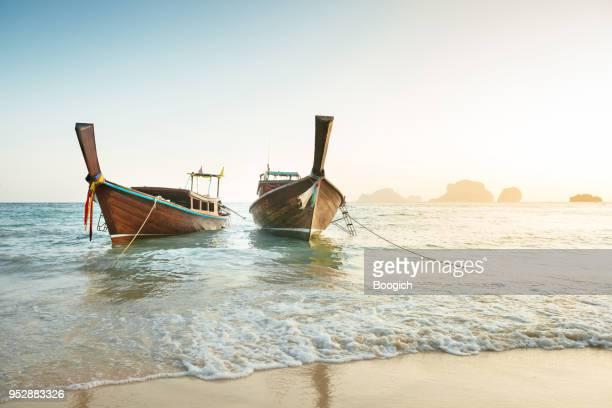 hölzerne longtail boote in tropical railay beach in krabi thailand - thailändische kultur stock-fotos und bilder