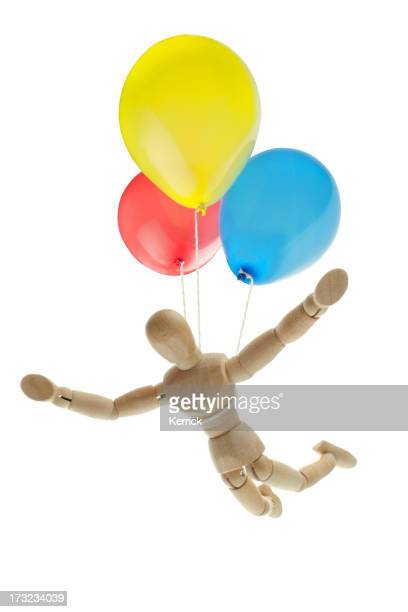 wooden mannequin flying with ballons